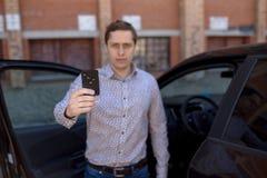 Ein Mann, der nahe einem Auto steht und einen Autoalarmschlüssel hält Stockbilder