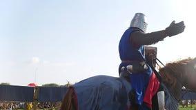 Ein Mann in der Rüstung und in einem Umhang des Blaus ein Pferd reiten reitet hinter das Publikum, begrüßt Leute stock video