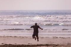 Ein Mann, der in Richtung zum Ozean auf einem Strand läuft und einen großen Sprung macht lizenzfreies stockfoto