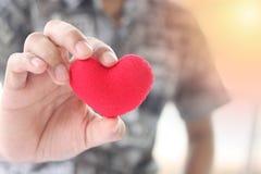 Ein Mann, der ein rotes Herz in seiner Hand hält stockbild