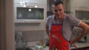 Ein Mann, der ein Schutzblech trägt, um Lebensmittel zu kochen Kleiden Sie und binden Sie ein rotes Küchenschutzblech Möchte eine stock footage
