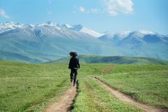 Ein Mann in der schwarzen Kleidung, die entlang die Landstraße in Richtung zu den Bergen läuft stockbild