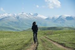 Ein Mann in der schwarzen Kleidung, die entlang die Landstraße in Richtung zu den Bergen läuft lizenzfreies stockfoto