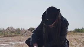 Ein Mann in der schwarzen Kleidung läuft die Wüste durch und findet etwas Abfall stock footage