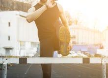 Ein Mann in der schwarzen Kleidung trainiert drau?en mit einer Sperre Eignungsathlet auf dem Sportfeld Training mit H?rde Im bott stockfotos
