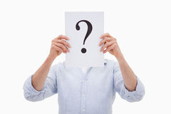 Ein Mann, der sein Gesicht hinter einem Fragezeichen versteckt Stockbilder