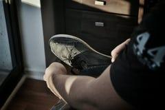 Ein Mann, der an seine Schuhe setzt stockbilder