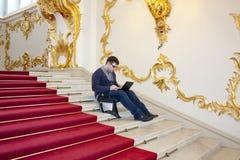Ein Mann, der an seinem Laptop auf dem Haupttreppenhaus des Winter Palastes arbeitet Die Einsiedlerei Unkonventionelle Arbeitsplä Lizenzfreies Stockbild