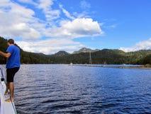 Ein Mann, der sich vorbereitet, sein Boot an einem Dock auf Alexander Island, auf Gambier-Insel, in Howe Sound anzukoppeln, Briti lizenzfreie stockfotografie