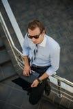 Ein Mann in der Sonnenbrille und mit einem Laptop Lizenzfreie Stockbilder