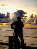 Ein Mann, der Sonnenuntergangmoment genießt Stockfotografie