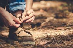 Ein Mann, der Spitze während Trekking in einem tropischen Wald bindet stockbilder