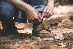 Ein Mann, der Spitze während Trekking in einem tropischen Wald bindet stockfotos