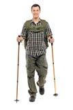 Ein Mann in der Sportkleidung mit Rucksack und wandern Polen lizenzfreie stockbilder