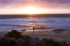 Ein Mann, der stoppt, um den Sonnenuntergang anzustarren Stockfotografie