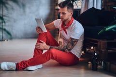 Ein Mann, der Tablet-PC in einem Raum mit Dachbodeninnenraum verwendet Lizenzfreies Stockbild