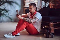Ein Mann, der Tablet-PC in einem Raum mit Dachbodeninnenraum verwendet Stockfotos