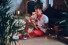 Ein Mann, der Tablet-PC in einem Raum mit Dachbodeninnenraum verwendet Lizenzfreie Stockfotografie
