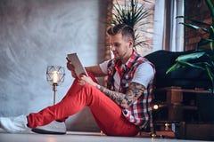 Ein Mann, der Tablet-PC in einem Raum mit Dachbodeninnenraum verwendet Stockfoto