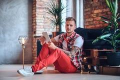 Ein Mann, der Tablet-PC in einem Raum mit Dachbodeninnenraum verwendet Stockbild