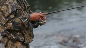 Ein Mann in der Tarnungskleidung fischt für das Spinnen stock footage