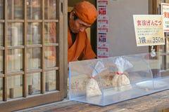 Ein Mann, der Taschen des Snacks verkauft, nannte Genkotsu-ame in Takayama, Stockbild