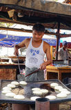 Ein Mann, der traditionelle Kuchen am Markt in Bagan, Myanmar kocht Stockfoto