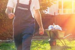Ein Mann in der Uniform geht für einen Besen Im Hintergrund ist ein Wagen mit Abfalltaschen T?nung und Licht lizenzfreie stockbilder
