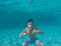 Ein Mann, der unter Wasser im Pool schwimmt Stockbilder