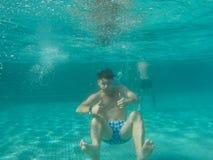 Ein Mann, der unter Wasser im Pool schwimmt Stockfotografie