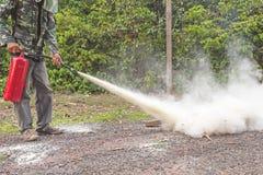 Ein Mann, der wie man einen Feuerlöscher demonstriert, benutzt Lizenzfreie Stockfotografie