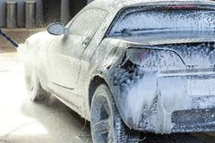 Ein Mann dient sein Auto auf einer Wanne, anwendet einen aktiven Schaum stockfoto