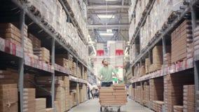 Ein Mann drückt eine Laufkatze voll von Kästen auf ihr zwischen Regale mit Pappschachteln in einem Speicherlager stock video footage