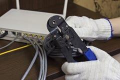 Ein Mann drückt einen Chip auf einem Netzkabel, ein Modem, das Internet, ein Nahaufnahmenetz zusammen stockfotos