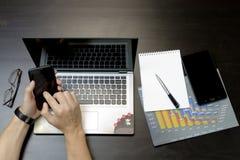 Ein Mann druckt auf einem Laptop und liegt nahe bei dem Telefon, Tablette glasse Stockbilder