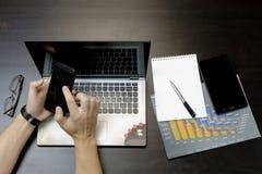 Ein Mann druckt auf einem Laptop und liegt nahe bei dem Telefon, Tablette glasse Lizenzfreie Stockbilder