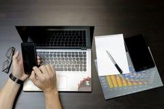 Ein Mann druckt auf einem Laptop und liegt nahe bei dem Telefon, Tablette glasse Stockfoto