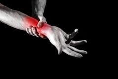 Ein Mann, eine Frau, die ihr schmerzliches Handgelenk, die Schmerz erfahrend, a hält Stockbild