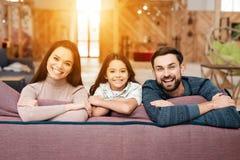 Ein Mann, eine Frau und ihre kleine Tochter werfen auf der Kamera beim Sitzen auf der Couch auf lizenzfreie stockfotografie
