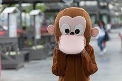 Ein Mann in einem Affekostüm steht auf der Straße Stockfotografie