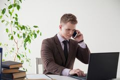 Ein Mann in einem Anzug arbeitet an einem Schreibtisch mit einem Computer und Büchern im Büro Stockbilder