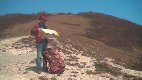 Ein Mann in einem Cowboyhut, in einer Lederjacke, in Blue Jeans und in Gl?sern steht in den Bergen und betrachtet eine Reisendkar