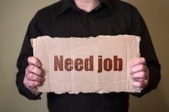 Ein Mann in einem dunklen Hemd, das ein Stück Pappe mit Text Bedarfs-Job hält lizenzfreies stockbild