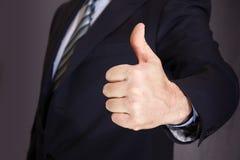 Ein Mann in einem dunklen Mantel hält Hand mit dem Daumen oben Stockfotografie