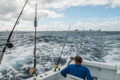 Ein Mann in einem Fischerboot in einem stürmischen Ozean mit Blick auf die Küste von Miami Stockfotos