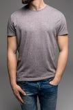 Ein Mann in einem grauen T-Shirt und in den Denim hält seine Hände in den Taschen lizenzfreies stockfoto