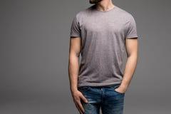 Ein Mann in einem grauen T-Shirt und in den Denim hält seine Hände in den Taschen stockbilder