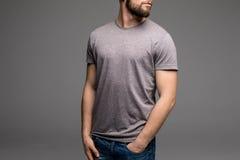 Ein Mann in einem grauen T-Shirt und in den Denim hält seine Hände in den Taschen lizenzfreie stockfotos