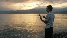 Ein Mann in einem Hemd überprüft Mitteilungen auf der Tablette während des Sonnenaufgangs auf dem Strand des Ozeans Wunderbare Fa stock footage