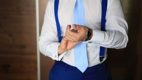 Ein Mann in einem Hemd und in einer Bindung, setzt seine Hand auf die Uhr Hochzeit GR stock footage